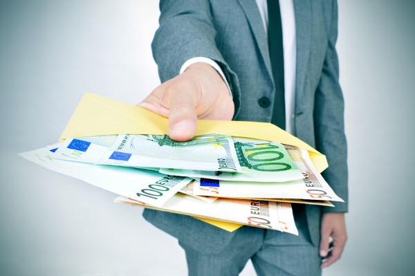 a man in suit giving an envelope full of euro bills