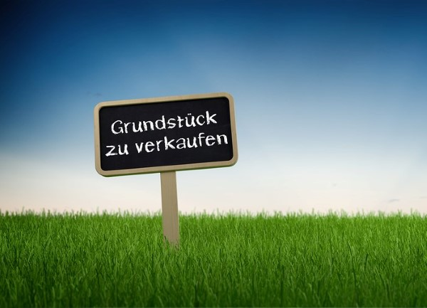 Sign Posted in Long Green Grass in front of Blue Sky with Rising