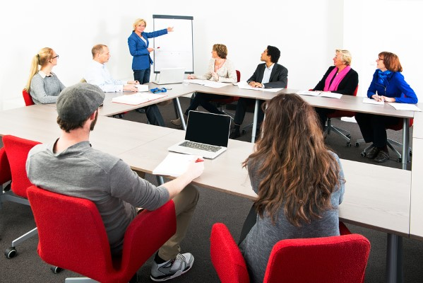 Several businesspeople meeting in a spaceous meeting room for a