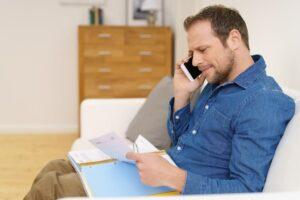 Mann prüft Akten und telefoniert